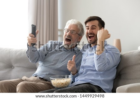 Excited old father and son watching tv, eating popcorn snack, having fun at home, family fans watching football or soccer match together, celebrating favorite team win, goal, sitting on couch