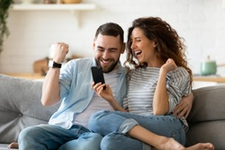 Excited overjoyed couple resting on couch holding smart phone celebrating on-line lottery win, bid betting victory moment, unbelievable opportunity or invitation, internet sale, getting prize concept