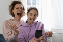 Excited overjoyed family young adult mom and teenage girl daughter feeling euphoric winning using smartphone at home. Happy parent and child getting great ecommerce sale offer, celebrating success.