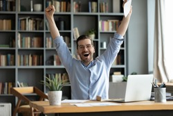 Excited overjoyed man received good news in letter, job promotion or great exam result, happy businessman or student celebrate success, shouting, raising hands, sitting at workplace with laptop