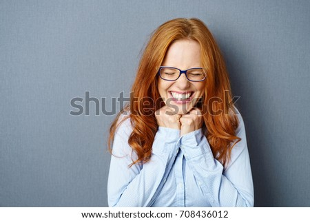 Excited overjoyed young woman wearing glasses beaming with happiness and screwing up her eyes as she holds her fists to the over a blue studio background with copy space #708436012