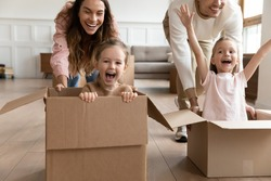 Excited parents push little 6s 7s daughters cute kids sitting inside of carton boxes compete in races, happy family spend active playtime at new house at relocation day. Funny quarantine time concept