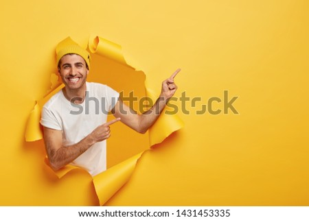 Excited pleased young man in casual outfit, shows something great on blank space, advertises product, poses in torn hole in yellow paper wall, empty area for your advertising content or promotion