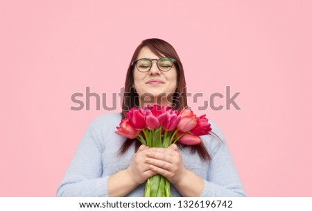 Excited plump woman in glasses embracing bouquet of tulips being happy with 8 March present