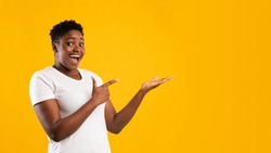 Excited Plus-Size Black Woman Showing Invisible Object Pointing Fingers Aside Advertising Your Text Posing Standing On Yellow Studio Background, Smiling To Camera. Blank Space, Panorama