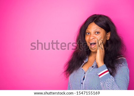 excited plus size young african woman screaming out lound standing in a pink wall. advert concept