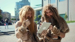Excited prehistoric bushmen of hunter-gatherers covered in fur browsing internet on tablet discovering technology in modern city. Adaptation concept.