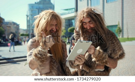 Excited prehistoric bushmen of hunter-gatherers covered in fur browsing internet on tablet discovering technology in modern city. Adaptation concept. Stock photo ©