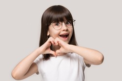 Excited preschool small adorable girl wearing eyeglasses, showing love sign, isolated on grey studio background, better eyesight vision concept. Head shot close up little cutie making heart gesture.