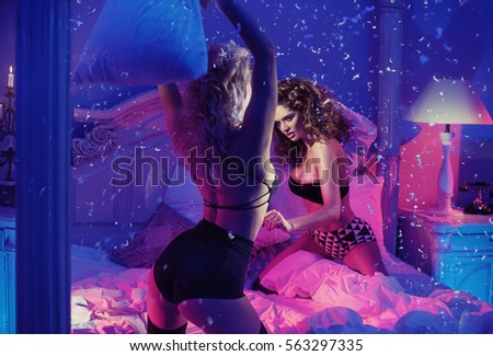 Excited pretty women fighting with pillows in bedroom