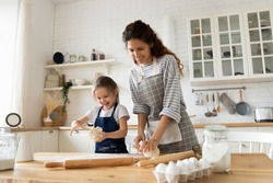 Excited pretty young woman in apron making homemade pastry with cute small child daughter. Smiling little preschool girl playing with dough, enjoying cooking process with happy mother in kitchen.