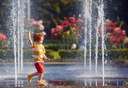 excited redhead baby boy having fun between water jets, in fountain. Summer in the city