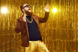 Excited rich red-haired young man in neck chain and cool glasses having fun at glamour night club disco party. Happy fashionable bearded showman singing and dancing on stage with golden background