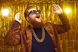 Excited rich redhead man in bling golden neck chain and cool glasses DJing and having fun at glamour party. Happy fashionable showman with beard and handlebar mustache singing and dancing on stage
