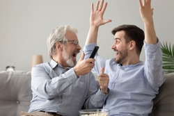 Excited 60s father and grown up millennial son sitting on couch eating pop corn watching sport match on TV celebrating favourite football team victory screaming with joy, common boyish hobbies concept
