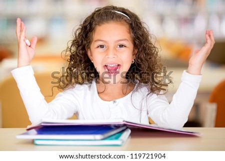 Excited school girl at the library looking surprised
