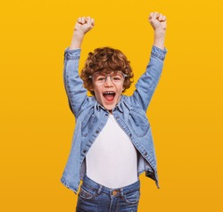 Excited schoolboy in casual wear standing with fists up on yellow background while screaming and celebrating achievement