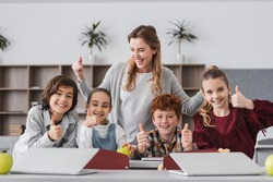 excited schoolkids and teacher showing thumbs up in classroom