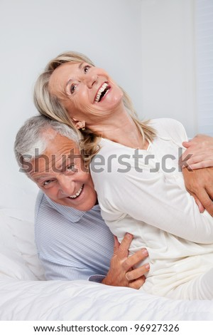 Excited senior couple laughing together on bed