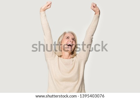 Excited senior woman raised stretched hands open mouth laughing screaming with joy feels happy isolated on grey studio background, weekend no stress euphoric lucky lady celebrating lottery win concept #1395403076