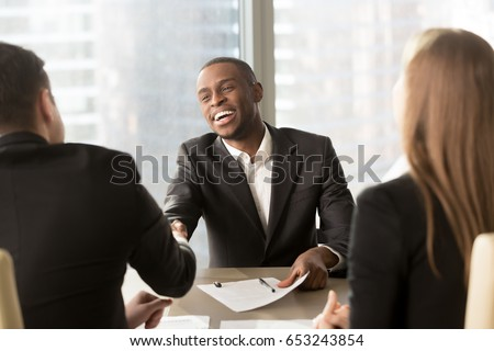 Excited smiling black businessman handshaking white partner at meeting, successful african applicant getting hired, got a job, satisfied multiracial businessmen shaking hands after signing document