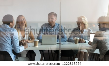 Excited smiling employees listening to African American colleague at company meeting, diverse team discussing business strategy, sharing startup ideas in boardroom view through glass wall