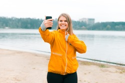 Excited smiling girl is making a selfie or video chating outdoors near a park lake.
