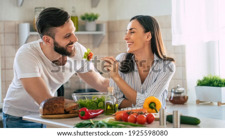 Excited smiling young couple in love making a super healthy vegan salad with many vegetables in the kitchen and man testing it from a girl's hands