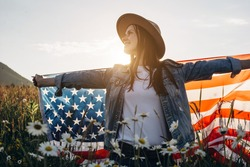 Excited smiling young woman sitting on flowers field holding usa flag under sunset sky happy looking aside. Hipster lady in hat enjoying beautiful summer nature. 4th of July and patriotic holiday