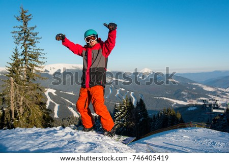 Excited snowboarder standing on the slope with his arms in the air in victorious gesture copyspace emotions recreation happiness positivity people recreational resort Bukovel #746405419