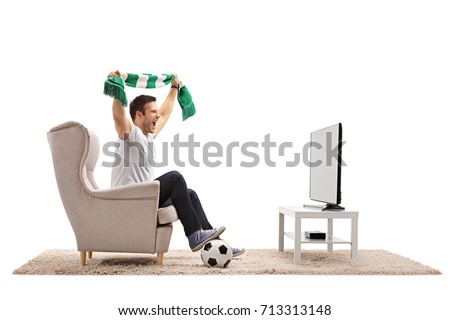 Excited soccer fan with a scarf sitting in an armchair and watching a match on television isolated on white background