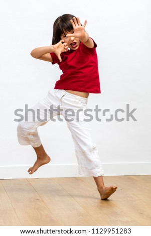 excited sporty young child with dynamic gesture fighting, showing energetic grace and power with dancing legs and hands for kid's martial art over wooden floor, white background #1129951283