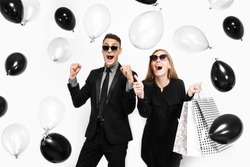 Excited stylish couple, a man in a suit and a girl in a dress, in her hands, balloons and bags, for shopping, rejoice, waiting for a holiday, on a white background. Black Friday
