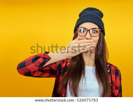 Excited surprised young woman covers hands open mouth over yellow background. Emotional female portrait. Hipster girl. #526075783