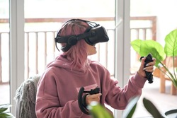 Excited teen girl pink hair wears vr headset goggles holds controllers plays vr video game futuristic immersive simulator explores virtual reality 3d 360 cyber gaming experience sits in chair at home.