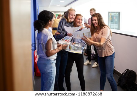 Excited Teenage High School Students Celebrating Exam Results In School Corridor