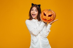 Excited teenage schoolgirl in uniform holding halloween pumpkin isolated over orange background