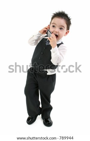 Excited toddler boy in suit speaking on cellphone.  Shot in studio over white.