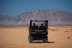 excited tourists driving away for buggy safari trip through the mountain desert