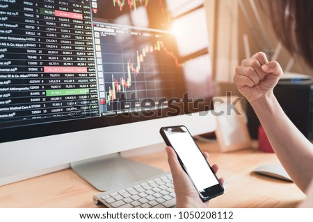 Excited trader woman looking at portfolio with mobile phone