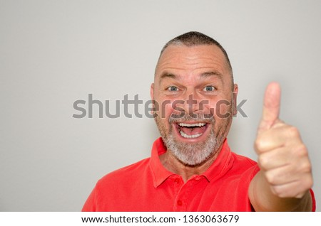 Excited triumphant man in red shirt giving a thumbs up gesture with his hand signalling his jubilation at good news over a light grey studio background with copy space