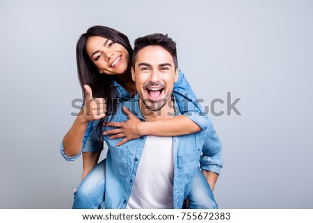 excited two people in love is having fun, they adore each other. Pretty joyful lovely smiling woman is sitting on her boyfriend's back and showing thumb up, they are isolated on grey background