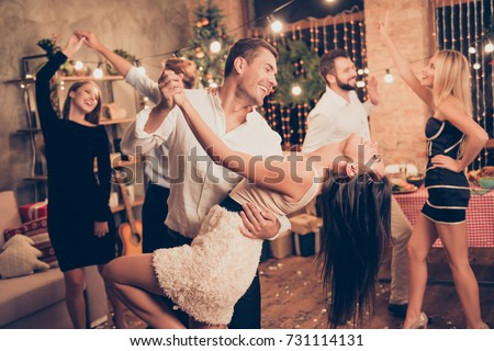 Excited, welldressed, cheerful, elegant husband holds cute wife, lean, she bending over, raised up leg, group of festive fancy luxury classy models with hot figures realx, enjoy, funky night