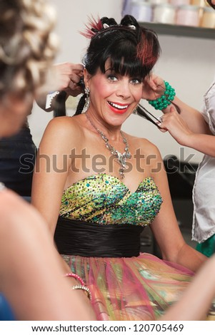 Excited white woman with stylists working in salon