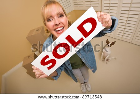 Excited Woman and Doggy with Sold Real Estate Sign Near Moving Boxes in Empty Room Taken with Extreme Wide Angle Lens.