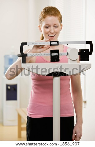 Excited woman checking dieting success by weighing herself on scale