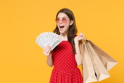 Excited woman girl in red summer dress, eyeglasses isolated on yellow background. People lifestyle concept. Hold package bag with purchases after shopping, hold fan of cash money in dollar banknotes