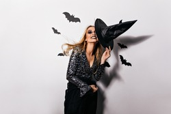 Excited woman in sparkle attire chilling at halloween party. Inspired blonde girl holding big black hat.
