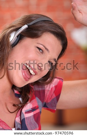 Excited woman listening to music through headphones