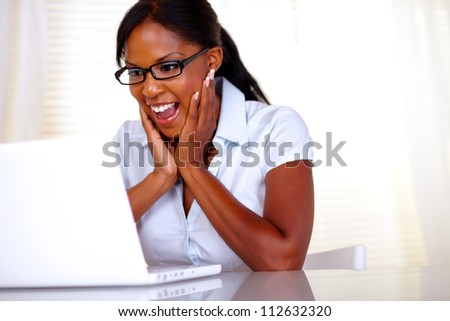 Excited woman looking to laptop screen with black glasses at workplace - copyspace